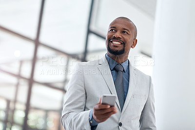 Buy stock photo Shot of a confident businessman using a smartphone in a modern office