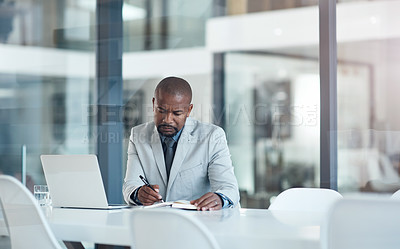 Buy stock photo Shot of a confident businessman writing in a notebook at his desk in a modern office