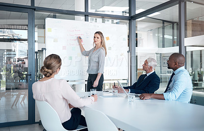 Buy stock photo Shot of a mature businesswoman delivering a presentation to her colleagues in a modern office