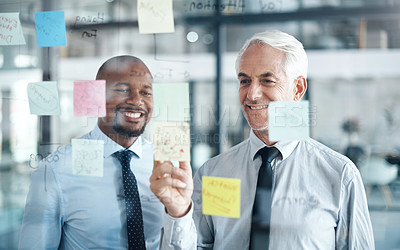 Buy stock photo Shot of two businessmen having a brainstorming session in a modern office