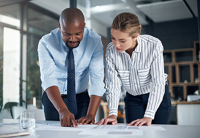 Buy stock photo Shot of two businesspeople going through paperwork in an office