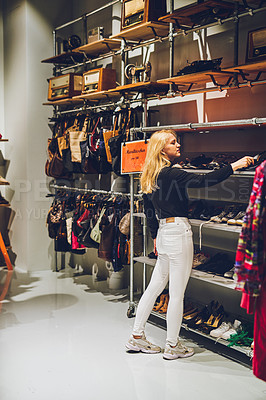 Buy stock photo Shot of a young woman shopping for shoes at a store