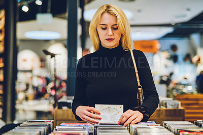 Buy stock photo Shot of a young woman shopping for CDs at a store