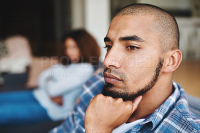 Buy stock photo Cropped shot of a handsome young man looking upset after an argument with his wife in their home