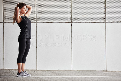 Buy stock photo Shot of a sporty young woman tying her hair while exercising outdoors