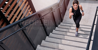 Buy stock photo High angle shot of a sporty young woman running up a staircase outdoors
