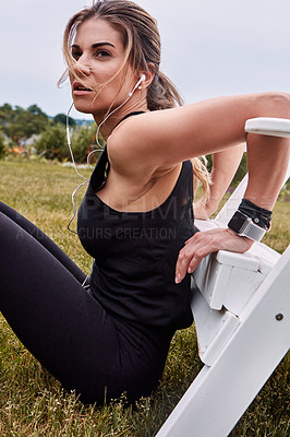 Buy stock photo Shot of a sporty young woman doing bench dips outdoors