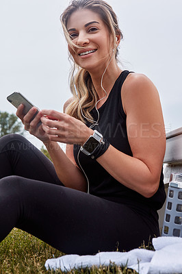 Buy stock photo Portrait of a sporty young woman using a cellphone while exercising outdoors