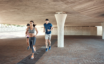 Buy stock photo Defocused shot of a small group of three people out for a run together