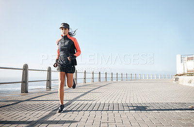 Buy stock photo Shot of an attractive woman out for a run on the promenade