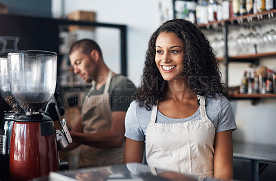 Buy stock photo Cropped shot of a young barista looking happy while standing behind the counter
