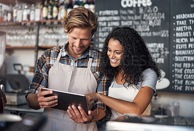 Buy stock photo Cropped shot of partners looking at something on a digital tablet in their cafe