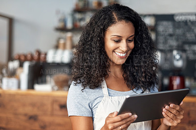 Buy stock photo Shot of a young shop owner using a digital tablet while standing in her cafe