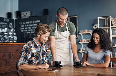 Buy stock photo Shot of a waiter serving two customers in a cafe