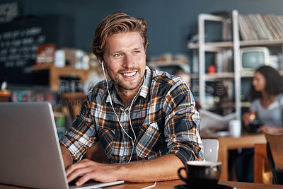 Buy stock photo Shot of a man wearing earphones while using his laptop in a cafe
