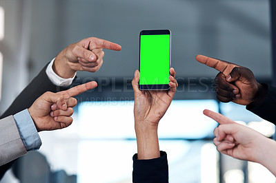 Buy stock photo Cropped shot of a group of businesspeople pointing at the green screen of a smartphone in a modern office