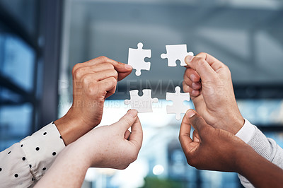 Buy stock photo Cropped shot of a group of businesspeople completing a puzzle