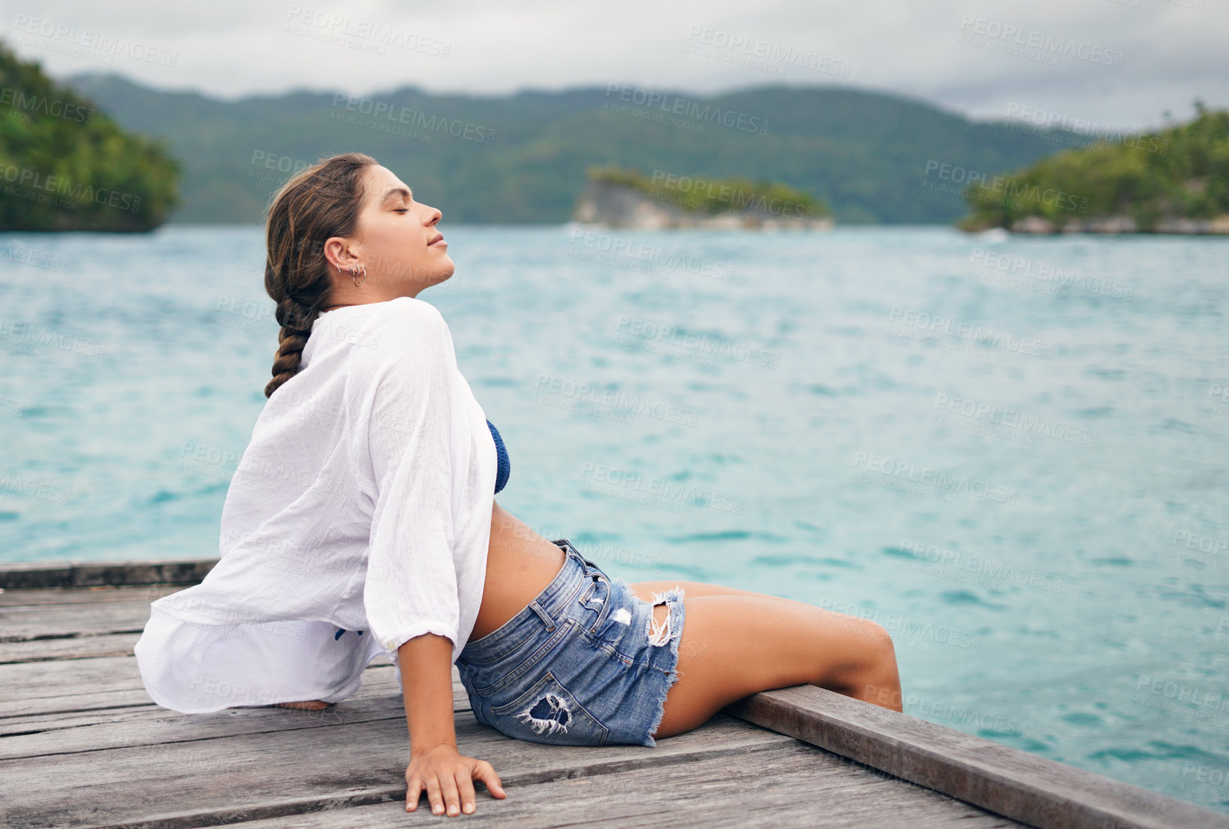 Buy stock photo Cropped shot of an attractive young woman sitting on the edge of a boardwalk and enjoying a breeze during vacation
