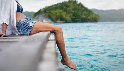 Buy stock photo Cropped shot of an unrecognizable woman sitting and dangling her legs over the edge of a boardwalk during vacation