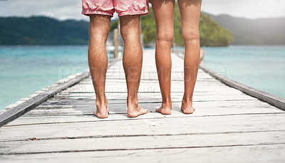 Buy stock photo Rearview shot of an unrecognizable couple standing on a boardwalk overlooking the ocean during a vacation