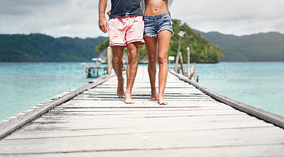 Buy stock photo Cropped shot of an unrecognizable couple walking down a boardwalk overlooking the ocean during a vacation