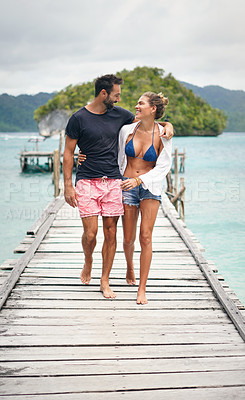Buy stock photo Full length shot of a happy young couple walking arm in arm down a boardwalk during a vacation together