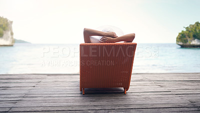 Buy stock photo Rearview shot of an unrecognizable woman sitting on a sun lounger alone during a vacation in Indonesia