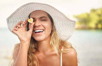 Buy stock photo Cropped portrait of an attractive young woman standing and playfully holding up a heart shaped pineapple piece against her eye