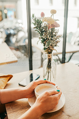 Buy stock photo Cropped shot of an unrecognizable woman sitting alone in a cafe and holding a cup of coffee
