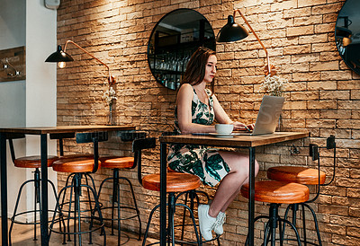 Buy stock photo Full length shot of an attractive young businesswoman sitting in a coffee shop alone and working on her laptop
