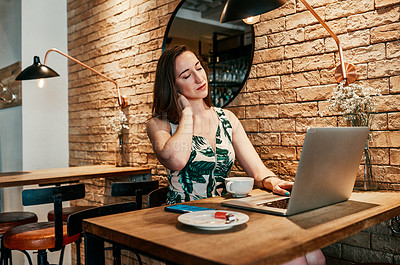 Buy stock photo Cropped shot of an attractive young businesswoman sitting in a cafe and suffering from neck ache while using her laptop
