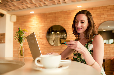 Buy stock photo Cropped shot of an attractive young woman sitting alone in a cafe and using her laptop for online shopping