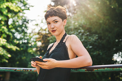 Buy stock photo Cropped portrait of an attractive young woman using a smartphone while standing in a park during the day