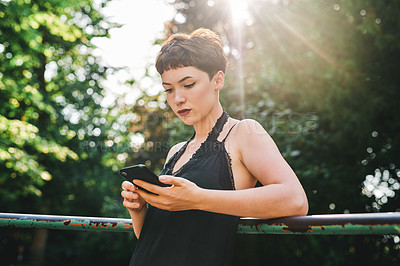 Buy stock photo Cropped shot of an attractive young woman using a smartphone while standing in a park during the day