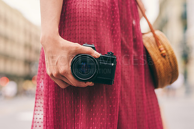 Buy stock photo Cropped shot of an unrecognizable woman standing alone and holding her camera while touring the streets of Spain