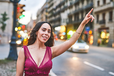 Buy stock photo Cropped shot of an attractive young woman standing alone and hailing a taxi while travelling through Barcelona alone