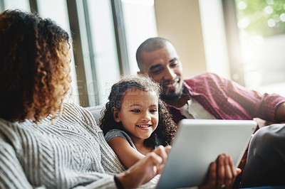 Buy stock photo Cropped shot of an adorable little girl using a digital tablet with her parents in their living room at home