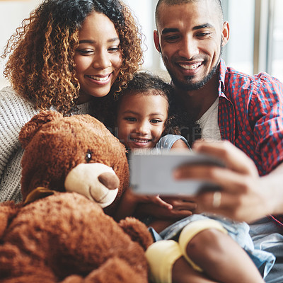 Buy stock photo Cropped shot of a happy young family of three taking selfies together in their living room at home