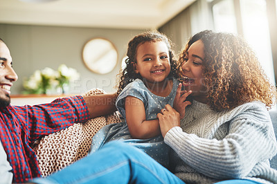Buy stock photo Cropped shot of an adorable little girl spending time with her parents in their living room at home
