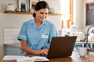 Buy stock photo Shot of a young nurse working on a laptop in a nursing home