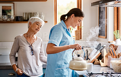 Buy stock photo Shot of a young nurse making a cup of tea for a senior woman in a retirement home