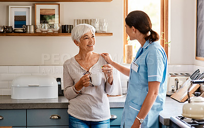 Buy stock photo Shot of a senior woman having tea while chatting to a young nurse in a retirement home