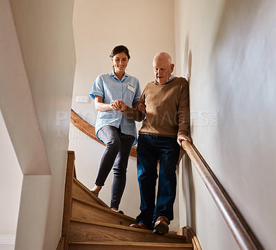 Buy stock photo Shot of a young nurse assisting a senior man down a staircase in a retirement home
