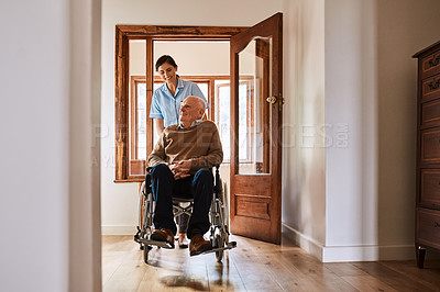 Buy stock photo Shot of a young nurse pushing a senior man in a wheelchair in a retirement home