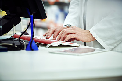 Buy stock photo Cropped shot of an unrecognizable pharmacist working on a computer