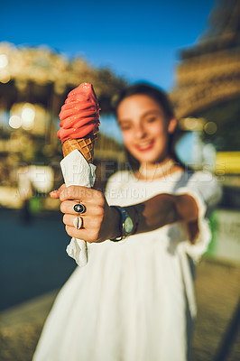 Buy stock photo Shot of a young woman eating ice cream at a carnival