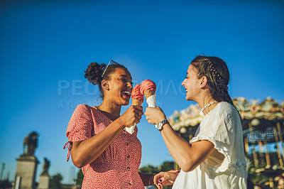 Buy stock photo Shot of two happy young women eating ice cream together at a carnival