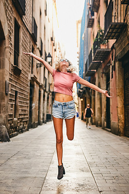 Buy stock photo Full length shot of an attractive young woman jumping for joy while touring the streets of Barcelona during a holiday