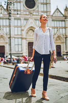 Buy stock photo Shot of a woman walking with her luggage in a foreign city