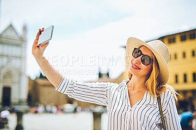 Buy stock photo Cropped shot of a woman taking a selfie while out exploring a foreign city